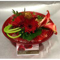 Λουλούδια σε κόκκινο γυάλινο βάζο με διακοσμητικά πετραδάκια.