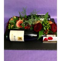 Flower arrangement on tray. (2) Bottles of wine.