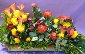 Διακοσμητική σύνθεση με άνθη σε ξύλινο δίσκο και χρωματιστά σφουγγάρια