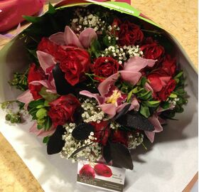(20) red roses A' quality Dutch gift wrapped with greens.Special with cymbidium orchids.