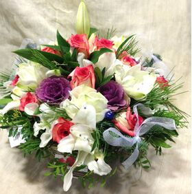 White flowers and christmas greens in basket with accessories