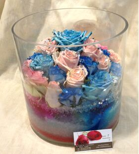 Arrangement of multi colored roses  in vase with decorative colored sand layers!!! Exclusive