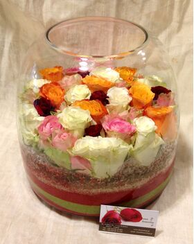 Arrangement of multi colored roses  in vase with decorative colored sand layers!!!