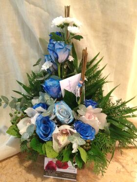 Arrangement with blue colored roses.