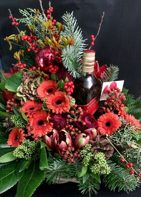 Christmas arrangement in a basket with chocolates and drinks