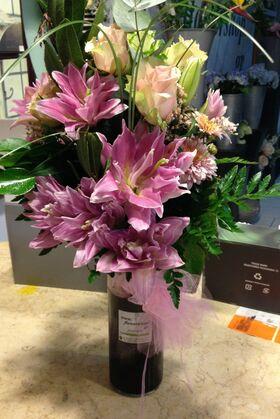 Ανθοπωλείο . Μπουκέτο με άνθη εποχής σε  γυάλινο βάζο με στρώσεις χρωματιστής διακοσμητικής άμμου