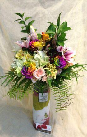 Ανθοπωλείο . Μπουκέτο με άνθη εποχής σε  γυάλινο βάζο με στρώσεις χρωματιστής διακοσμητικής άμμου - Special