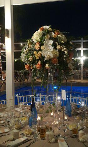Σύνθεση με λουλούδια επιτραπέζια με βάση ψηλό γυάλινο βάζο.